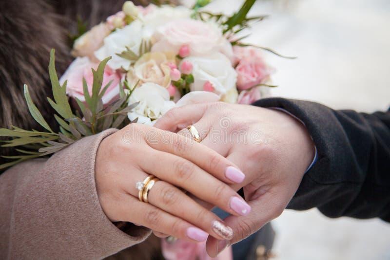 Härliga vigselringar på händerna av nygifta personerna royaltyfria foton