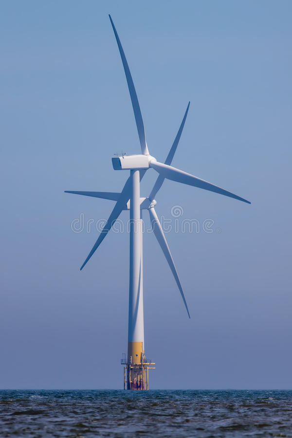 Härliga vindturbiner Korsade rotorblad av frånlands- windfarmturbiner arkivbild