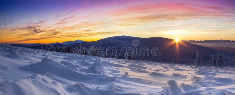Härliga vinterberg i det färgrika ljuset av resningsolen royaltyfria foton