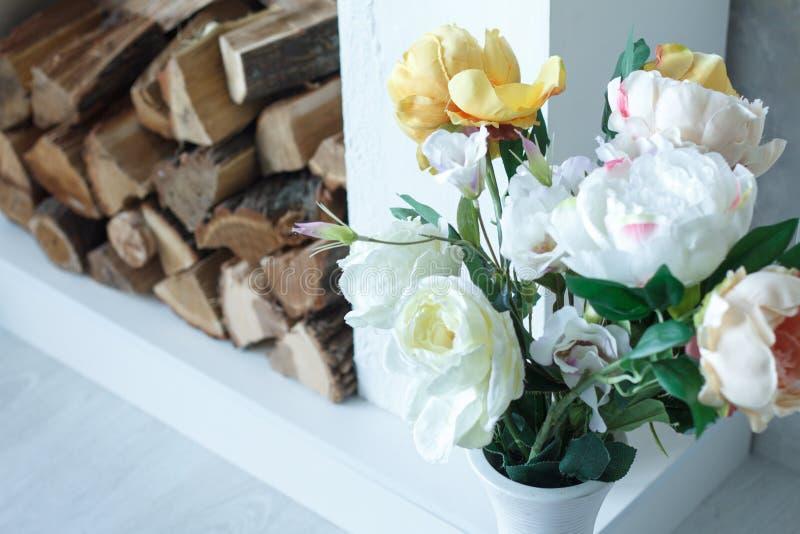 Härliga vita och gula vårblommor på bakgrunden av spisen, vedträ i spisen royaltyfri bild