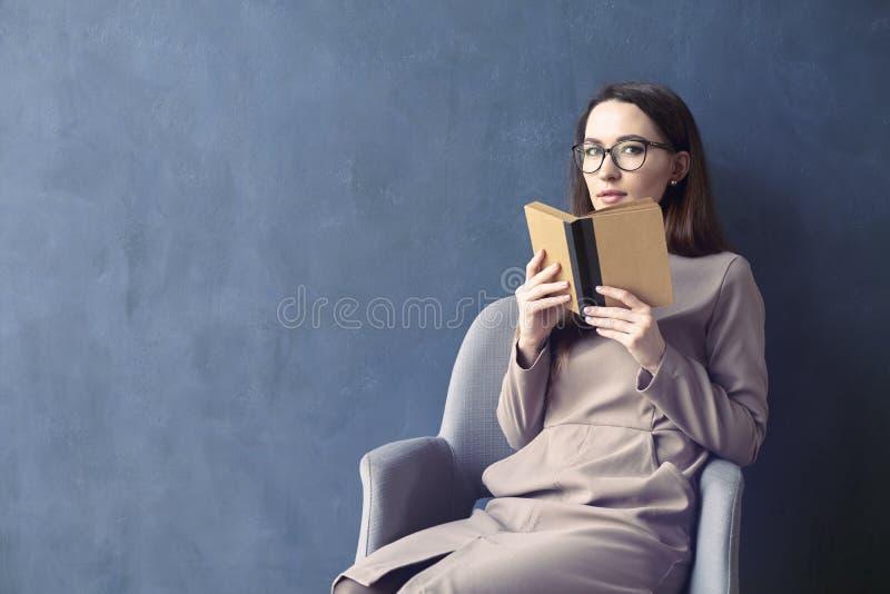 Härligt affärskvinnasammanträde i bok för tappning för vindkontor läs- Öppnad bokbrunträkning Mörker - blå väggbakgrund, dagljus fotografering för bildbyråer
