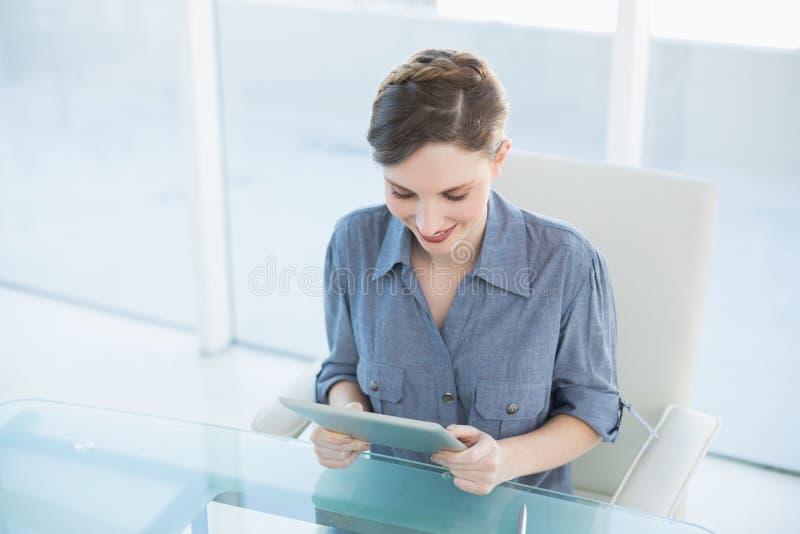 Härligt affärskvinnasammanträde på hennes skrivbord genom att använda hennes minnestavla arkivfoto