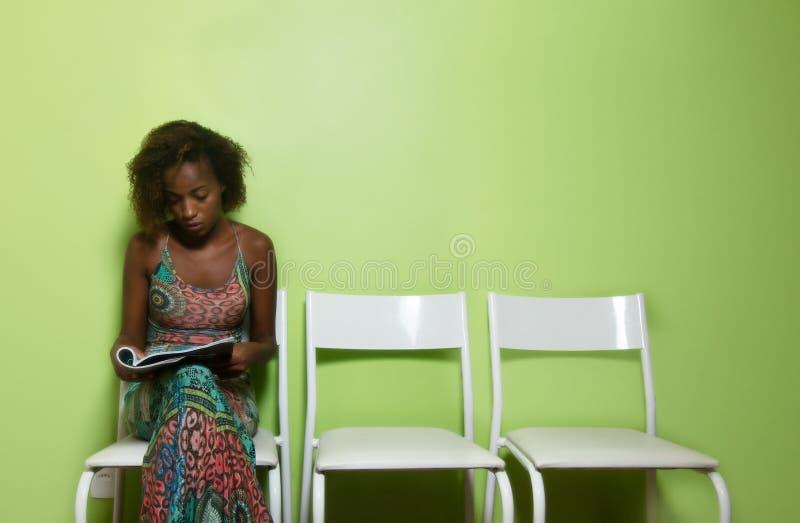 Härligt afrikansk amerikankvinnasammanträde på stol och läs- mor arkivfoto