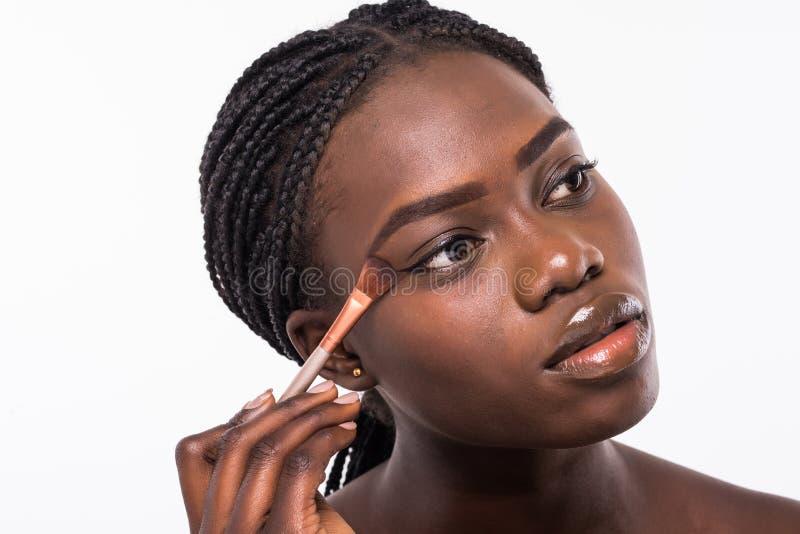 Härligt afrikanskt applicera för flicka rodnar på hud som isoleras på vit arkivbilder