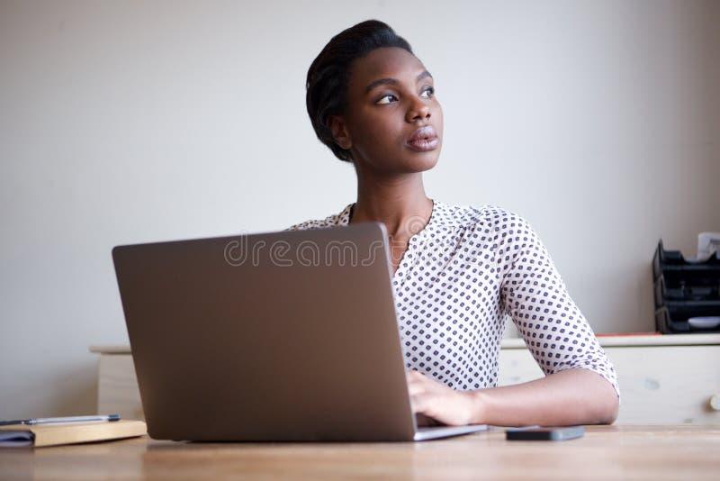 Härligt allvarligt kvinnasammanträde på skrivbordet med bärbara datorn royaltyfria foton