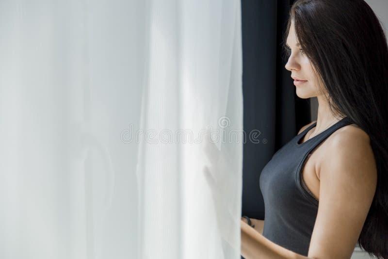 Härligt anseende för ung kvinna bredvid ett fönster royaltyfria bilder