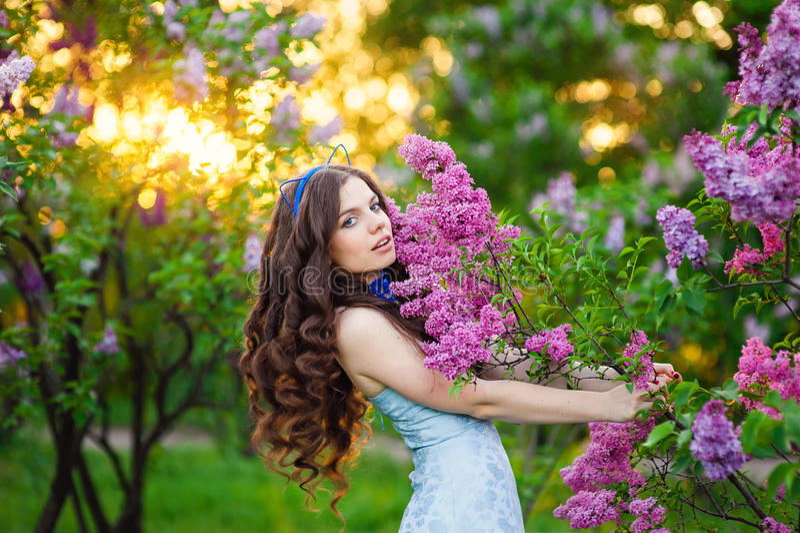Härligt anseende för ung kvinna i trädgården med en filial av li arkivbilder