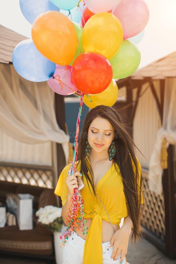 Härligt anseende för ung kvinna med ballonger på den near pölen för träplankasäng royaltyfria foton