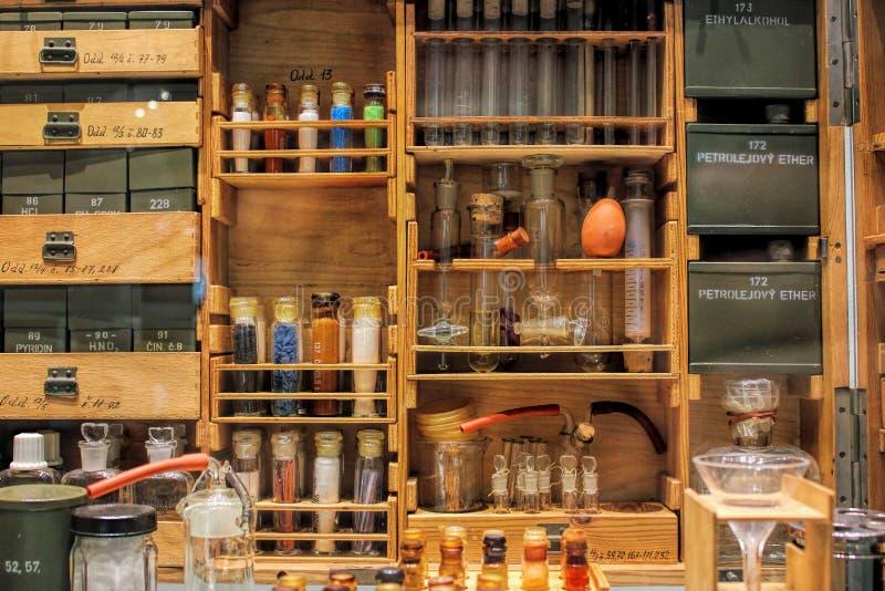 Härligt antikt apotek - gammalt skåp, färgrika flaskor som är smal arkivbild