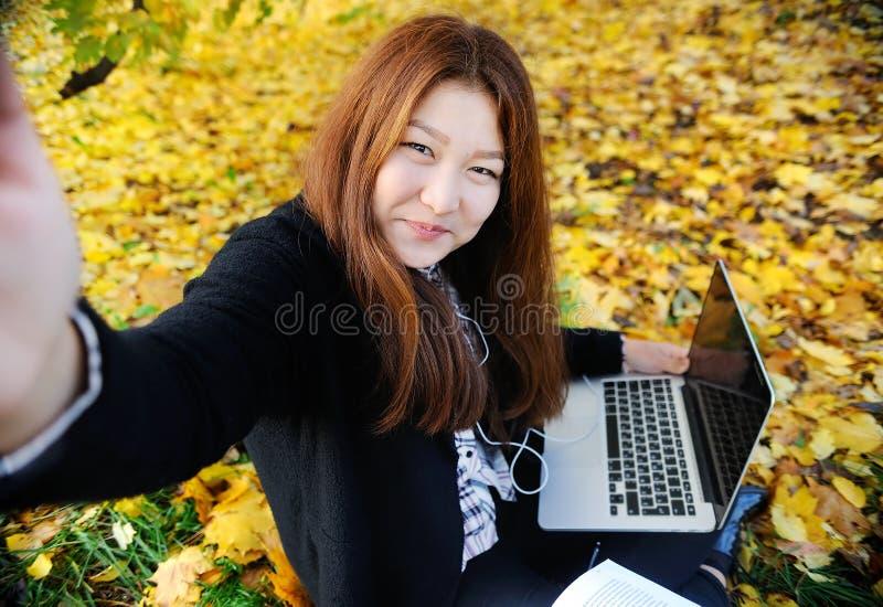 Härligt asiatiskt foto för selfie för studentflickadanande genom att använda hennes smartphone royaltyfri fotografi