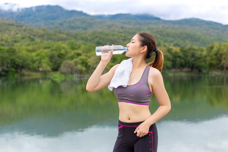Härligt asiatiskt idrottsman nenkvinnadricksvatten under hennes avbrott från morgonövning på en sjö parkerar med sikt av sjön och royaltyfria bilder
