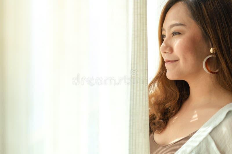 Härligt asiatiskt kvinnaanseende bredvid de vita gardinerna i morgonen royaltyfria bilder