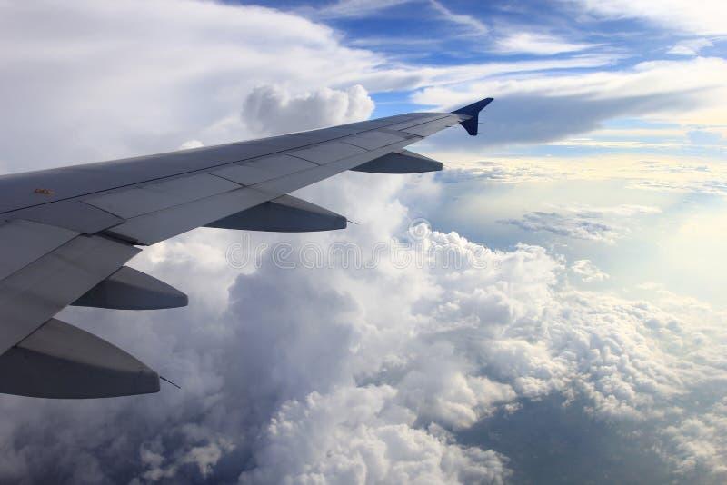 Härligt av flygplanvingen med moln och blå himmel på solnedgångli royaltyfria foton