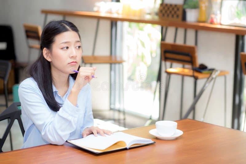 Härligt av idé för ung kvinna för ståendeaffär asiatisk tänkande och att skriva på anteckningsboken på tabellen arkivfoton