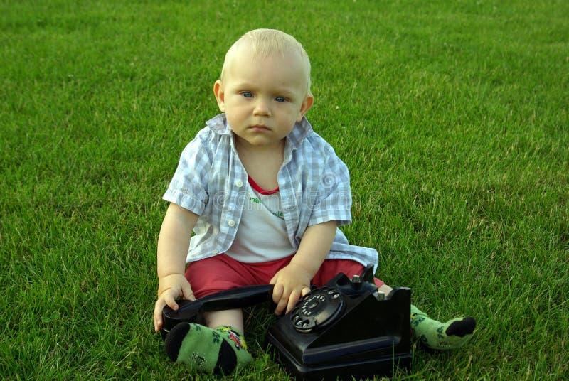 Härligt barn med telefonen på det gröna gräset fotografering för bildbyråer
