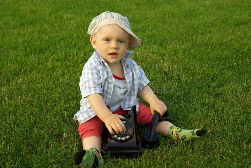 Härligt barn med telefonen på det gröna gräset royaltyfri foto