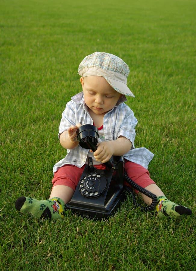 Härligt barn med telefonen på det gröna gräset royaltyfri fotografi