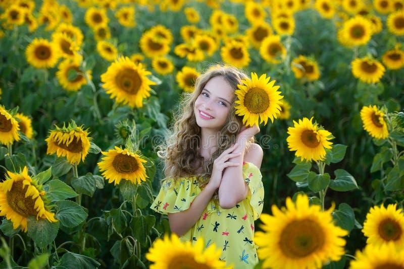 Härligt barn på fältet av solrosor fotografering för bildbyråer