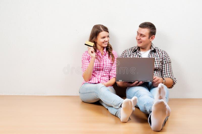 Härligt barn som älskar att shoppa för par som är online-, medan sitta på flooren tillsammans royaltyfri foto