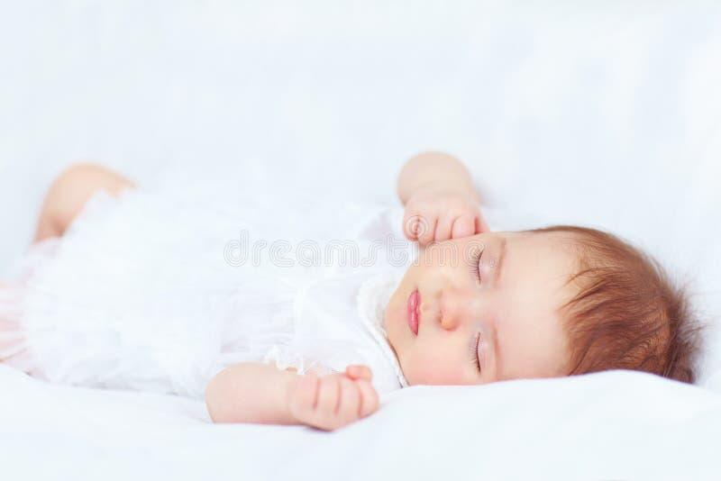 Härligt behandla som ett barn flickan som sover i säng, två gamla månader royaltyfri bild