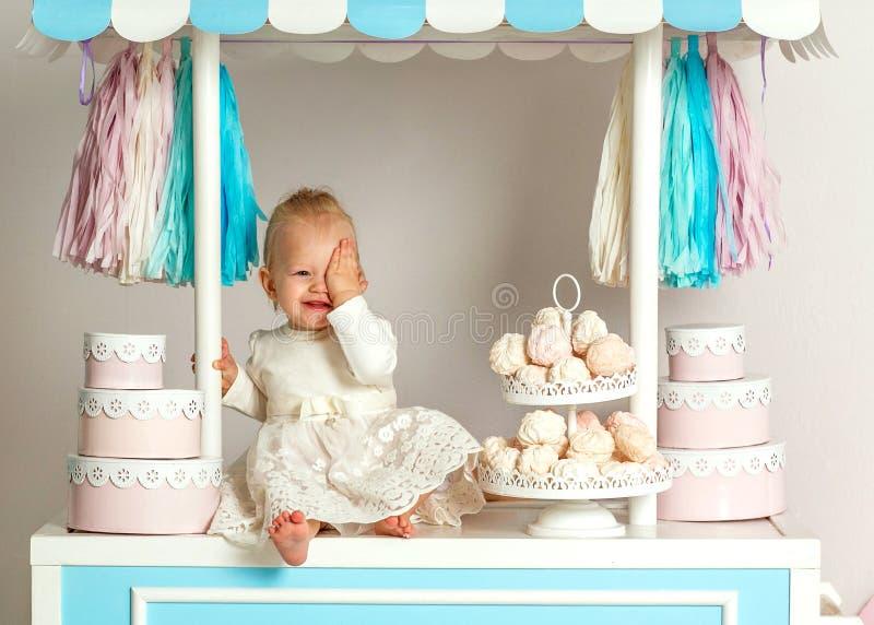 Härligt behandla som ett barn flickasammanträde nära det sagolika marshmallowhuset arkivbild