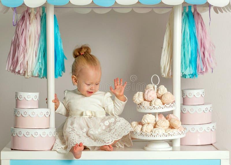 Härligt behandla som ett barn flickasammanträde nära det sagolika marshmallowhuset royaltyfri fotografi