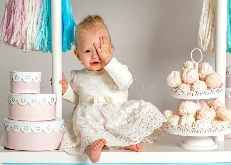 Härligt behandla som ett barn flickasammanträde nära det sagolika marshmallowhuset royaltyfri bild