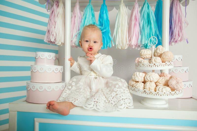 Härligt behandla som ett barn flickasammanträde nära det sagolika marshmallowhuset royaltyfri foto