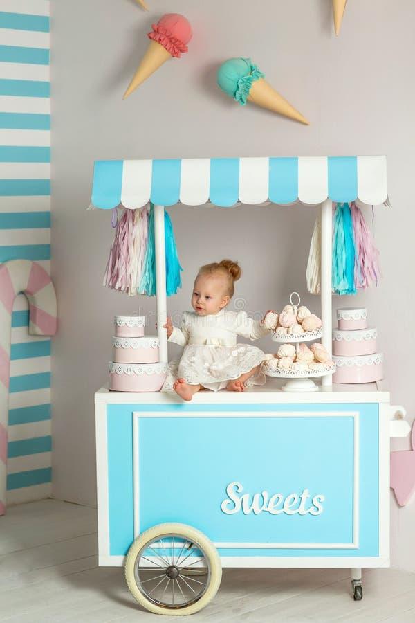 Härligt behandla som ett barn flickasammanträde nära det sagolika marshmallowhuset fotografering för bildbyråer