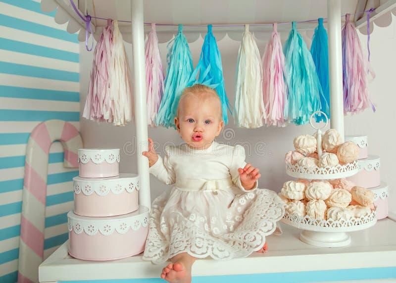 Härligt behandla som ett barn flickasammanträde nära det sagolika marshmallowhuset royaltyfria foton