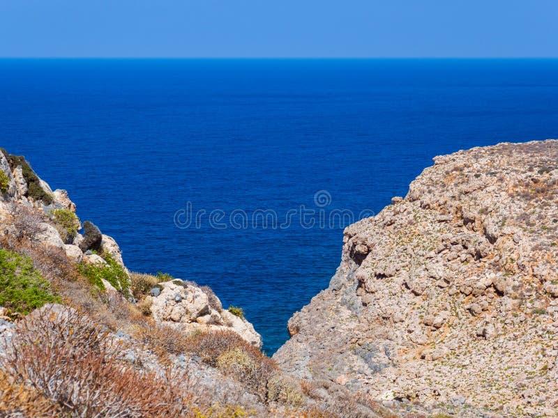 Härligt blått hav, steniga kullar i förgrunden arkivbild