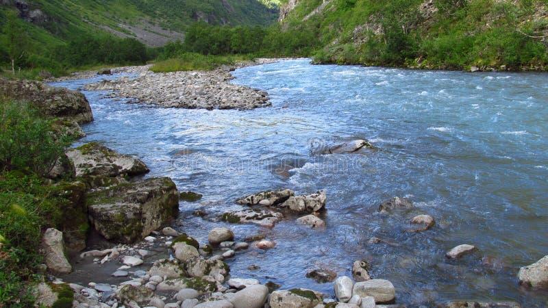 Härligt blått vatten i floden i den gröna vallen arkivfoto