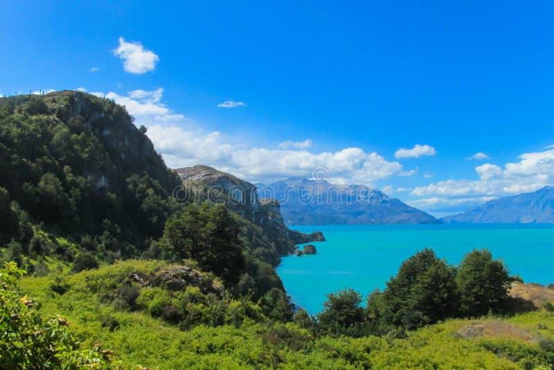 Härligt blått vatten och vaggar sjökusten arkivbilder