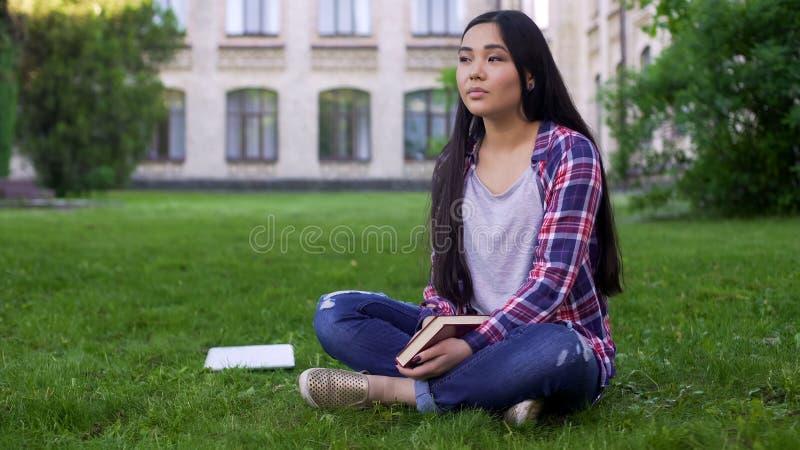 Härligt blandad-lopp flickasammanträde på gräsmatta nära högskolan och drömma om datum arkivfoton