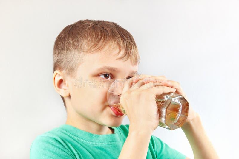 Härligt blont barn som dricker ny lemonad royaltyfri foto