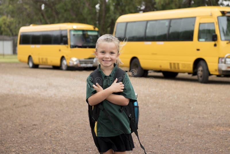 Härligt blont Caucasian le för ryggsäck för skolbuss för kvinnligt barn som väntande på bärande är lyckligt i studentung flicka o royaltyfri fotografi