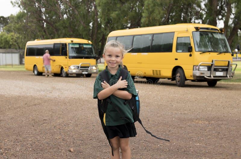 Härligt blont Caucasian le för ryggsäck för skolbuss för kvinnligt barn som väntande på bärande är lyckligt i studentung flicka o arkivfoto