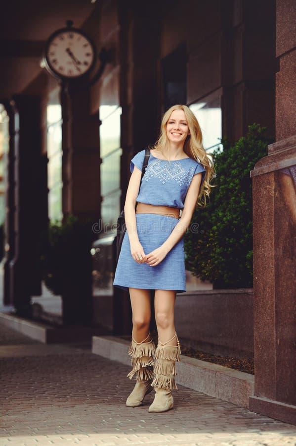 Härligt blont kvinnaanseende under huset med en iklädd stor klocka en blå klänning och kängor, blygsamt och blygt royaltyfri bild