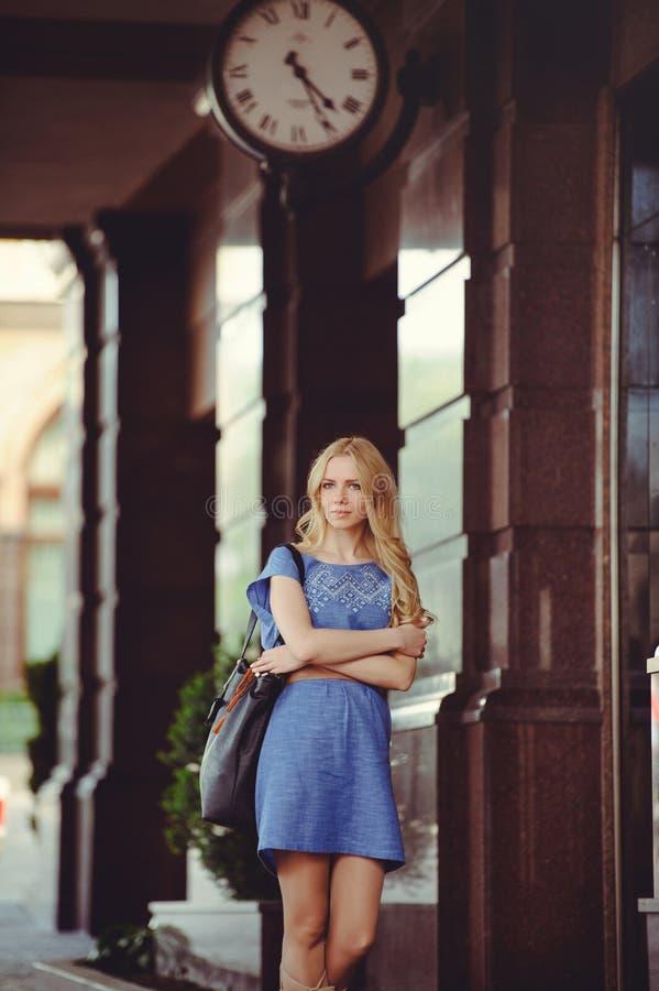 Härligt blont kvinnaanseende under huset med en iklädd stor klocka en blå klänning och kängor, blygsamt och blygt royaltyfri fotografi