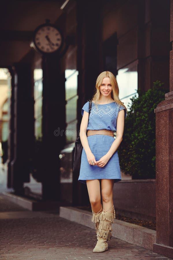 Härligt blont kvinnaanseende under huset med en iklädd stor klocka en blå klänning och kängor, blygsamt och blygt fotografering för bildbyråer