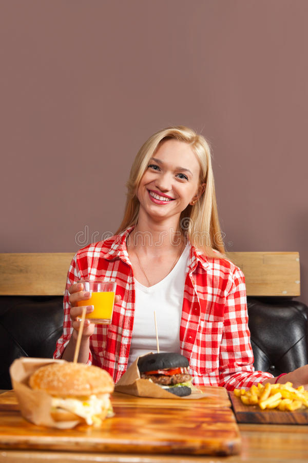 Härligt blont kvinnasammanträde i kaféhållen orange Juice Order Beef Burger Served i papper på trätabellen royaltyfria foton