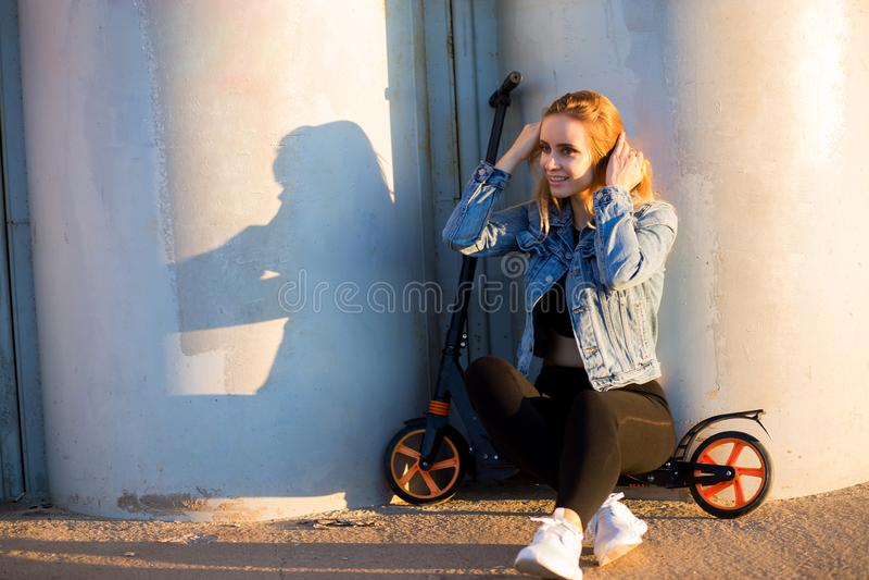 Härligt blont kvinnasammanträde på en sparkcykel nära väggen fotografering för bildbyråer
