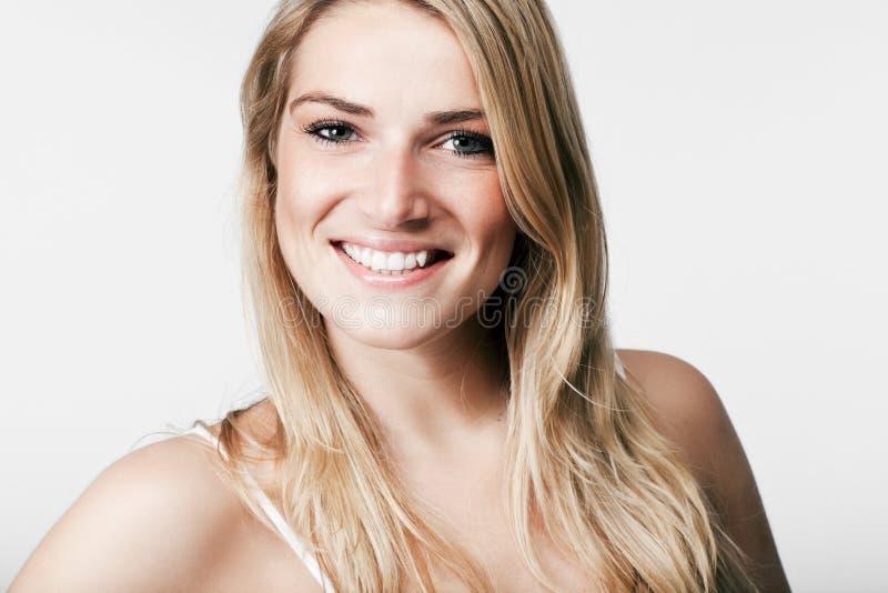 Härligt blont med ett livligt leende fotografering för bildbyråer