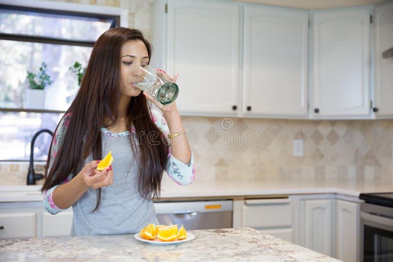 Härligt brunettdricksvatten från exponeringsglas på köket royaltyfri bild