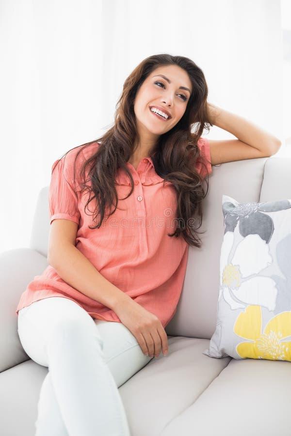 Härligt brunettsammanträde på hennes tänka för soffa royaltyfria bilder