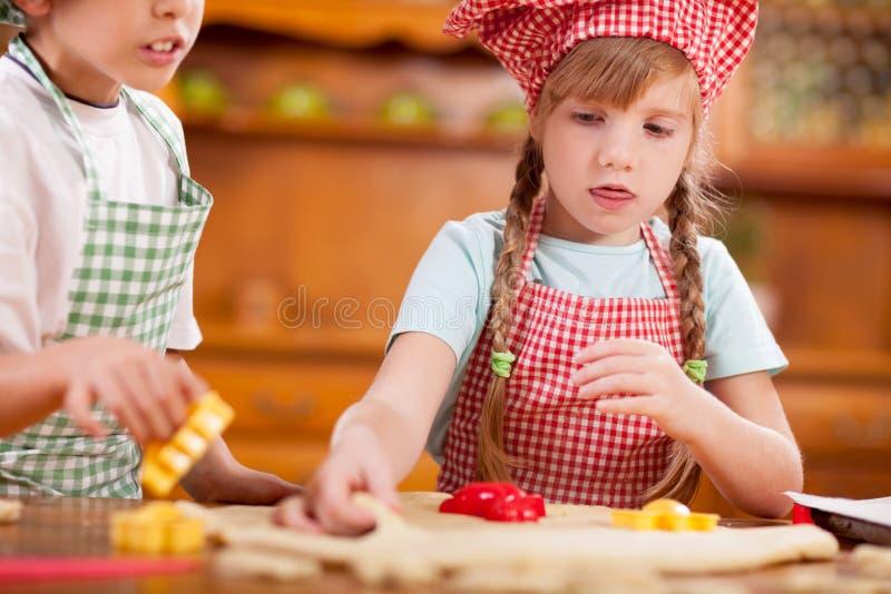Härligt caucasian barn som två gör en kaka royaltyfri foto