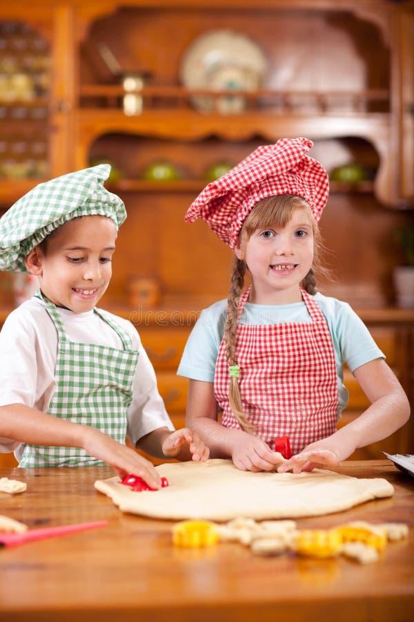 Härligt caucasian barn som två gör en kaka som lyckligt ler, royaltyfri foto