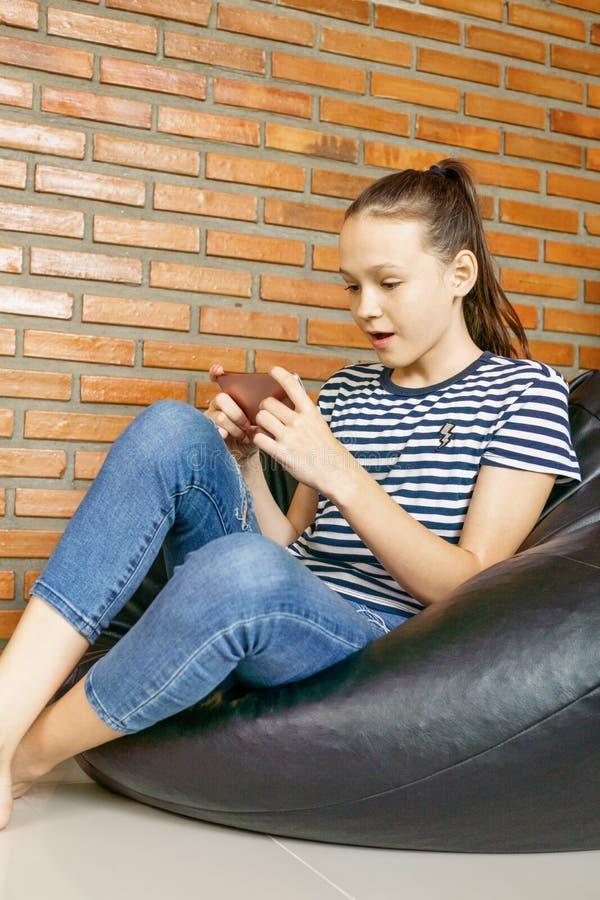 Härligt caucasian tonårigt flickasammanträde i stol för påse för svart böna med mobiltelefonen mot tegelstenväggen Tillfällig drä royaltyfria bilder