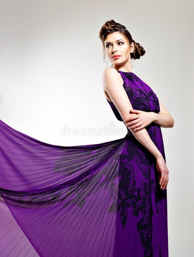 Härligt dana kvinnan i den violetta långa klänningen royaltyfri bild