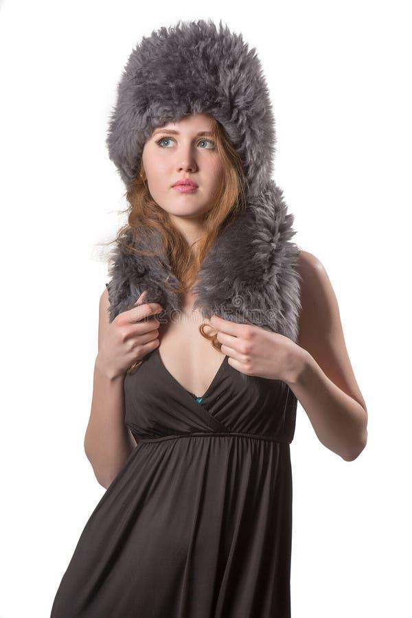 Härligt dana kvinnan som ha på sig en elegant svart klänning med kängan, och vintern pälsfodrar hatten arkivfoton